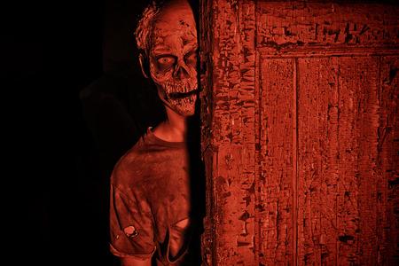 Beangstigend bloedige zombie man in bloedrood licht. Halloween. Stockfoto