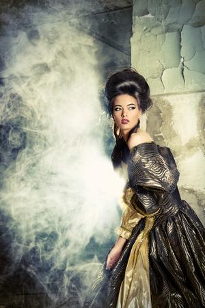 アート ファッション。エレガントな歴史的なドレスとバロッコ アップ スタイルの髪型の城の遺跡でポーズ美しい若い女性。ルネッサンス。バロッ