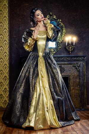 르네상스 스타일 - 고궁 내부의 무성한 비싼 드레스에 아름 다운 젊은 여자. 빈티지 스타일. 유행.
