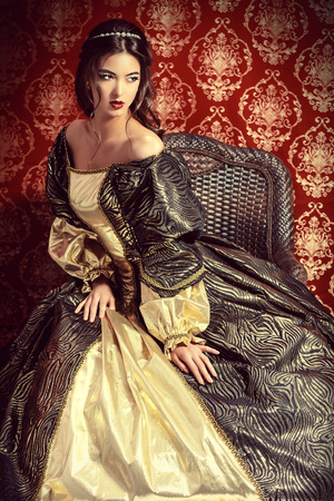 Full length portrait of a beautiful elegant lady in the lush expensive dress posing over vintage background. Renaissance. Barocco. Fashion. Foto de archivo