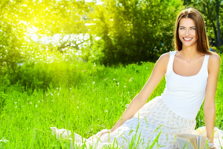 Beautiful smiling young woman sitting on a grass in the summer park. She is absolutely happy.