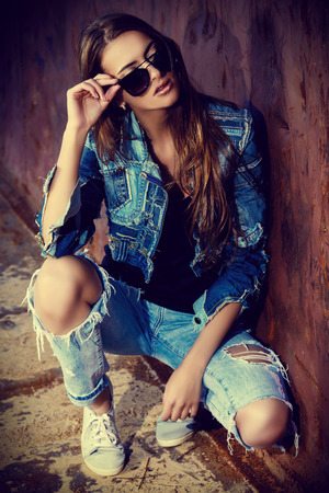 Stunning young woman in jeans clothes posing over urban background. Denim style. Fashion shot.