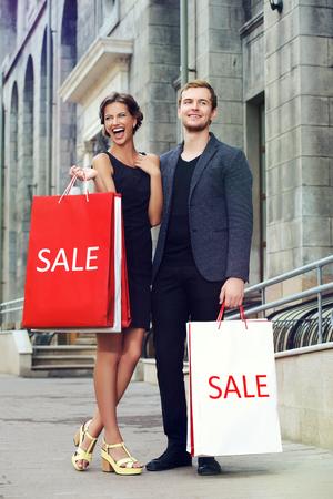 도시에서 매력적인 젊은 부부 쇼핑. 계절 판매. 패션 샷. 스톡 콘텐츠