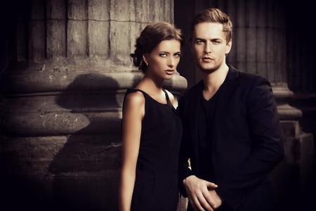 Fashion style photo of a beautiful couple over city background. Foto de archivo
