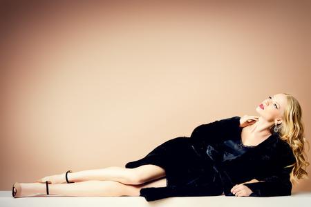 Bella donna bionda che indossa cappotto di pelliccia di visone. Moda, bellezza. Stile di vita lussuoso. Studio shot.