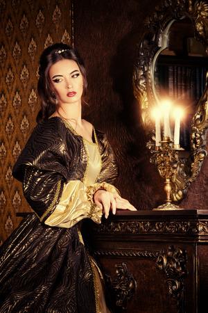 ルネサンス様式の古い宮殿内部の緑豊かな高価なドレスの美しい若い女性。ビンテージ スタイルです。ファッション。