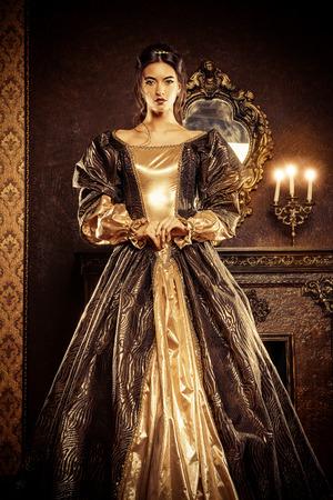 Estilo Renacimiento - hermosa mujer joven en el vestido caro exuberante en un antiguo palacio interior. Estilo vintage. Moda. Foto de archivo