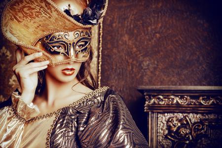 ベネチアの仮面カーニバル。美しい緑豊かなドレスとベネチアン マスクを身に着けているエレガントな女性は、宮殿の部屋に立っています。ルネッ