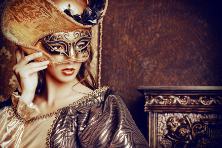 Venetiaanse carnaval. Elegante dame dragen prachtige, weelderige jurk en Venetiaans masker staat in een paleis kamer. Renaissance. Barocco. Mode.