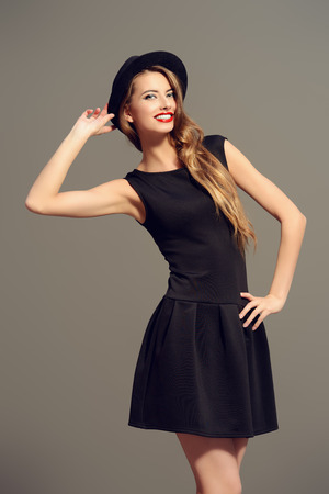 Joyful pretty girl wearing black dress and black classic hat smiling at camera. Beauty, fashion concept. Hipster style. Фото со стока