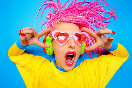Crazy expressive trendy DJ girl in bright clothes, headphones and bright dreadlocks