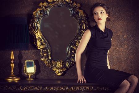 Mujer joven elegante en vestido de noche negro posando en interior de la vendimia