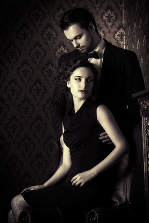 Black-and-white photo of a beautiful couple in elegant evening clothes in classic vintage apartments