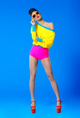 華やかなファッションのモデルは、鮮やかなカラフルな服とサングラスでポーズします。明るいファッション。光学・視力補助用品。スタジオ撮影 写真素材