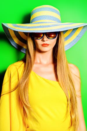 Mooie modieuze dame die fel gele jurk over groene achtergrond. Beauty, fashion concept. Optica. Zomervakantie. Stockfoto