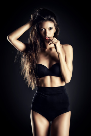 Beautiful slender woman alluring in black sexy lingerie. Fashion studio shot. Фото со стока