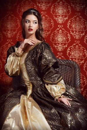 Señora joven hermosa en el vestido caro exuberante que presenta sobre el fondo de la vendimia. Renacimiento. Barocco. Moda. Foto de archivo