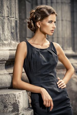 도시 배경 위에 검은 드레스 포즈를 입고 보그 모델. 패션 샷.