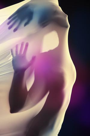 Vrouwelijke silhouet doorbreken van de witte stof over zwarte achtergrond. Kunstproject, theater. Moderne dans.