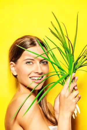 Joyful young woman with green onion over summer yellow background
