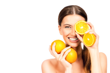 Joyful young woman holding juicy oranges before her eyes 스톡 콘텐츠