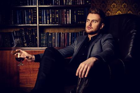 Elegancki mężczyzna w garniturze z szklanką napoju stoi w zabytkowe pokój