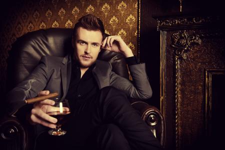Elegante man in een pak met een glas drank en sigaar in uitstekende ruimte