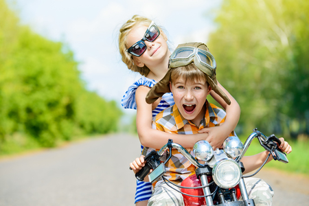 Happy kids go on a journey on a motorcycle on a bright sunny day 스톡 콘텐츠