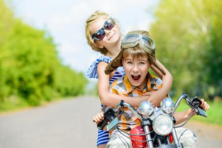 Gelukkig kinderen gaan op een reis op een motorfiets op een zonnige dag Stockfoto