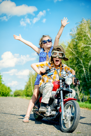 Happy kids go on a journey on a motorcycle on a bright sunny day Stock Photo