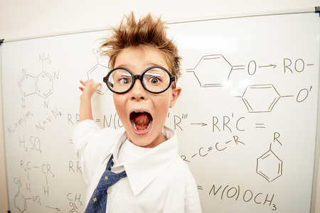 Funny schoolboy in big glasses standing by the school board and shouting. Chemistry. Science and education. 스톡 콘텐츠