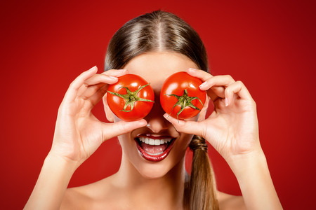 Beautiful laughing woman holding two ripe tomatoes before her eyes. Red background. Healthy eating concept. Diet. Stock Photo - 44127357