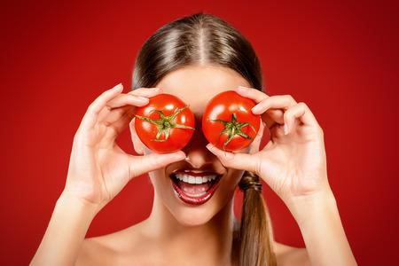 Bella donna che ride tenendo due pomodori maturi davanti ai suoi occhi. Sfondo rosso. concetto di mangiare sano. Dieta. Archivio Fotografico - 44127357