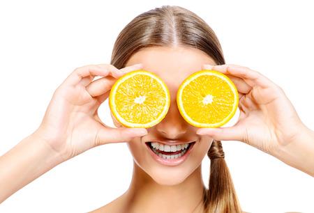 그녀의 눈 앞에 달콤한 오렌지를 들고 즐거운 젊은 여자. 건강한 먹는 개념. 다이어트. 화이트 이상입니다.