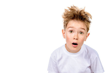 A boy in white t-shirt stares into the camera, he is surprised. Isolated over white background. Standard-Bild