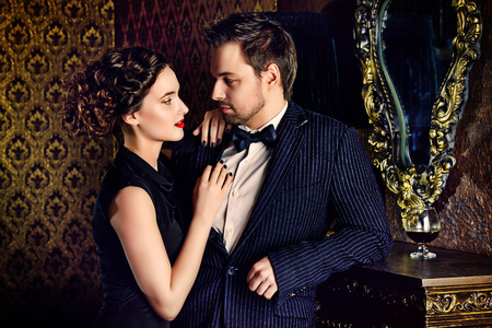 美しい男と女クラシック ビンテージ アパートで優雅な夜の服。グラマー、ファッション。愛の概念。