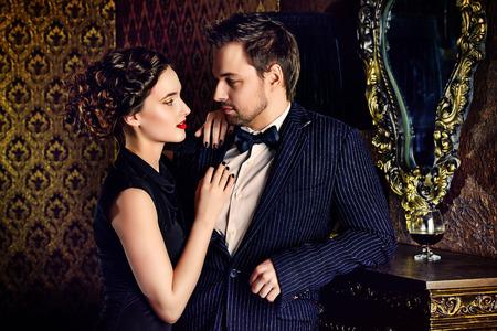 Hermoso hombre y mujer en ropa de noche elegantes en apartamentos de época clásica. Glamour, moda. Concepto del amor. Foto de archivo