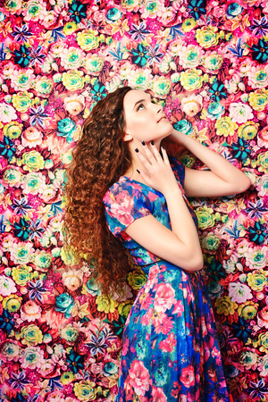 Beautiful tender woman in bright summer dress over floral background. Beauty, fashion. Stock Photo