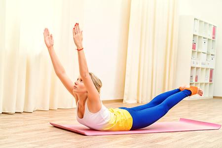 Slender athletic girl doing yoga exercises indoor. Professional trainer. Stock Photo - 44161109