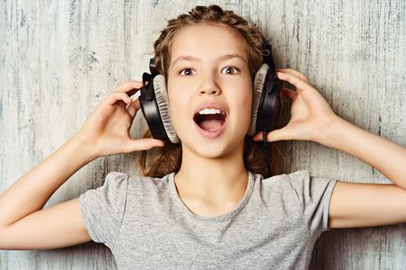 쿨 사춘기 소녀 헤드폰에서 음악을 즐긴다. 스튜디오 촬영. 스톡 콘텐츠