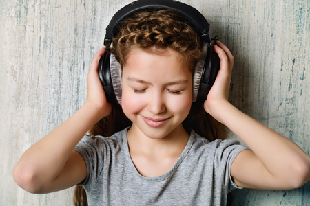 Cool teen girl enjoys the music in headphones.   Stock Photo