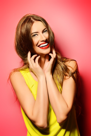 Happy emotional young woman in bright yellow dress laughing sincerely. Beauty, fashion concept. Hair, healthy hair. Stock Photo