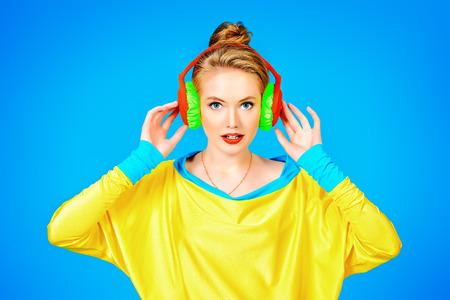 ヘッドフォンで音楽を聴いて明るいカラフルな服でトレンディな女の子。パーティー スタイル。スタジオ撮影をファッションします。 写真素材