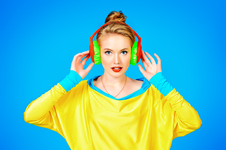 Trendy girl in bright colorful clothes listening to music in headphones. Party style. Fashion studio shot.