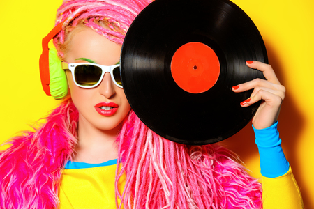 Glamorous modern DJ girl posing with vinyl record. Disco, party. Bright fashion.