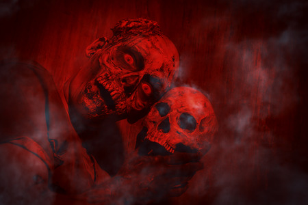 Frightening bloody zombie man with a skull in blood-red light. Halloween. Stock Photo