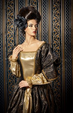 バロック様式のエレガントな歴史的なドレスとビンテージ背景にポーズ バロッコ髪型の美しい若い女性。ルネッサンス。バロッコ。ファッション。
