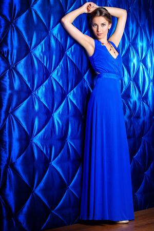 Ritratto di lunghezza completa di una bella donna in abito da sera elegante, in posa su sfondo vintage. Gioielleria. Moda girato. Acconciatura.