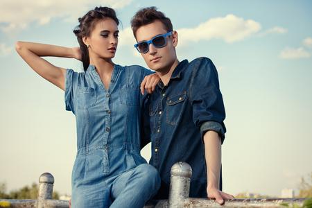 青い空にジーンズ服を着て現代若者の肖像画。ファッションを撮影しました。