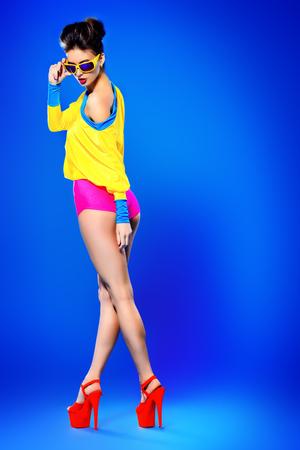 Mannequin glamour posant dans des vêtements et lunettes de soleil colorées vives. La mode Bright. Optique, lunettes. Studio, coup. Banque d'images
